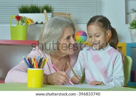 Grandmother with granddaughter drawing together - stock photo