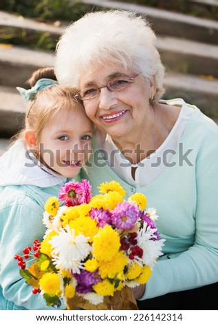 Grandmother with granddaughter holding flowers in the park - stock photo