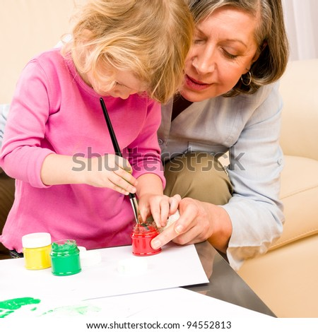 Grandmother with granddaughter playing together paint handprints on paper - stock photo