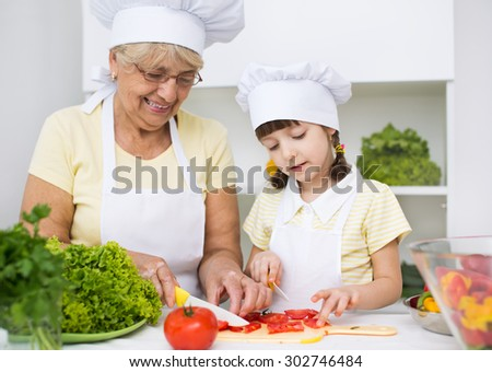 grandmother with granddaughter preparing a salad  - stock photo