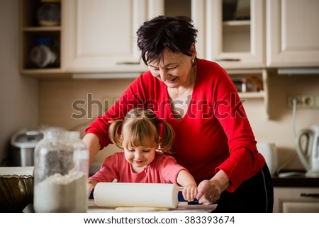 Grandmother with granddaughter preparing dough with rolling pin in kitchen - stock photo