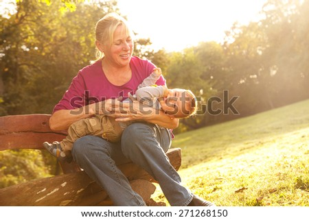 Grandmother with grandson in park - stock photo