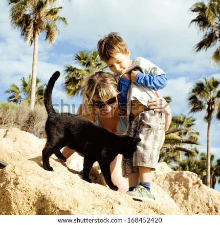 grandmother with grandson on cyprus beach among palms and rock playing with black cat - stock photo