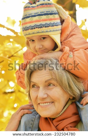 Grandmother with her granddaughter in the autumn park - stock photo