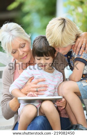 Grandmother with kids playing games on tablet - stock photo