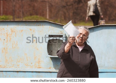 Grandmother with letter. Mature woman shows letter from postman. Happy pensioner. Emotional portrait - stock photo