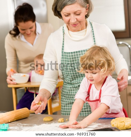 Grandmother with little girl prepare dough for baking in kitchen