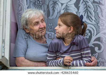 Grandmother with little granddaughter sitting in the window. - stock photo