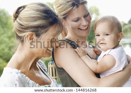 Grandmother with mother and daughter against the lake - stock photo