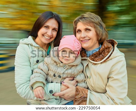 Grandmother with mother and daughter having fun on spinning roundabout. Autumn. Naturally blur motion - stock photo