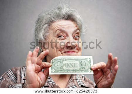 Grandmother with one dollar on a grey