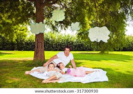 Grandmother with sleeping grandchildren under clouds in park - stock photo