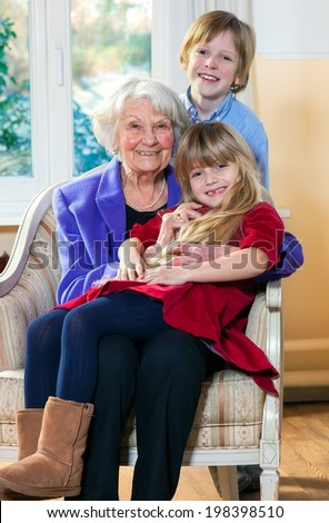 Grandmother with Two Children Having Fun indoors. - stock photo