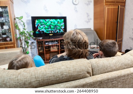 Grandmother with two young kids sitting on couch and watching tv at home - stock photo