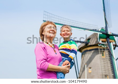 Grandother and grandson near windmill in Holland - stock photo
