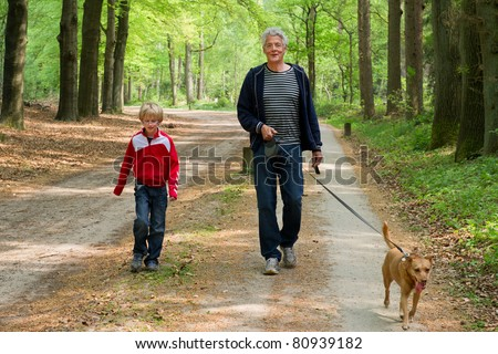 Grandpa and grandchild are walking the dog in the forest - stock photo