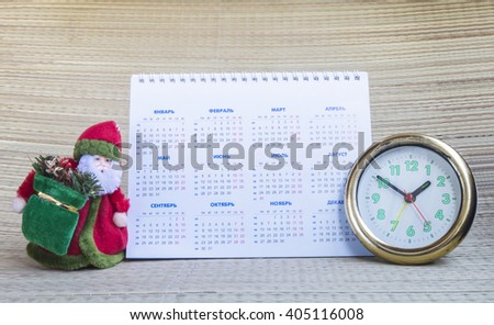 Grandparent Frost with paper calendar and round hour on beige background - stock photo