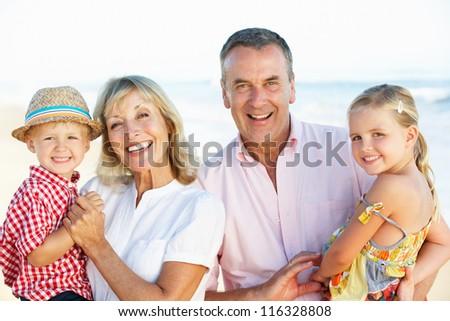 Grandparents And Grandchildren Enjoying Beach Holiday - stock photo
