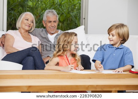 Grandparents and grandchildren on couch - stock photo