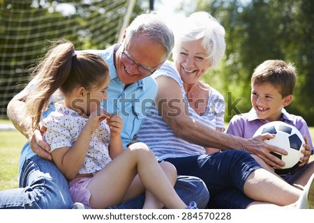 Grandparents And Grandchildren Playing Football In Garden - stock photo