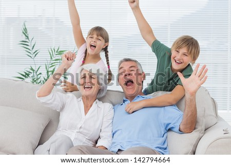 Grandparents and grandchildren raising arms in the living room - stock photo