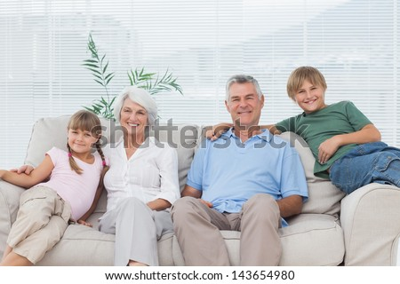 Grandparents and grandchildren sitting on couch in the living room - stock photo