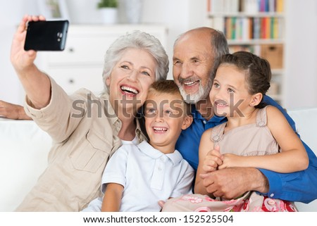 Grandparents and grandchildren sitting together in a close group on a sofa laughing and doing a self portrait with a hand held camera on a mobile phone - stock photo