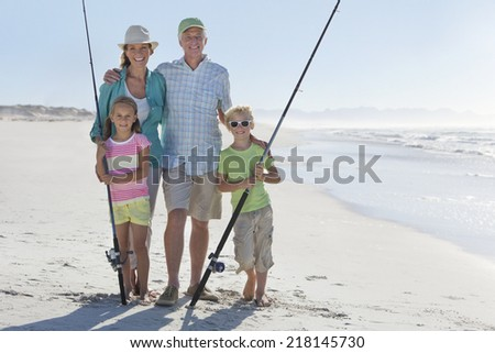 Grandparents and grandchildren with fishing rods on sunny beach - stock photo