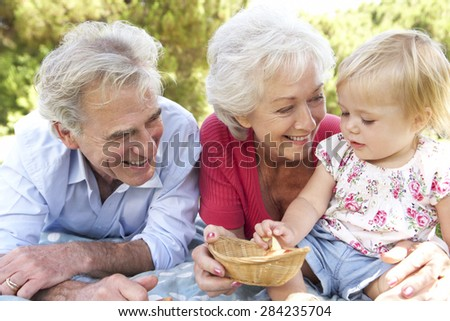 Grandparents And Granddaughter Enjoying Picnic Together - stock photo