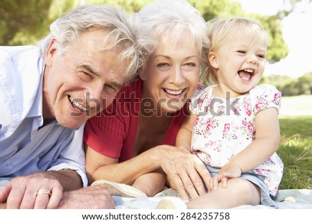 Grandparents And Granddaughter In Park Together - stock photo