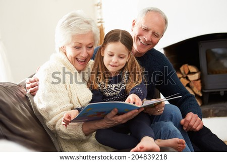 Grandparents And Granddaughter Reading Book At Home Together - stock photo