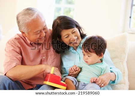Grandparents And Grandson Playing With Toy Together - stock photo