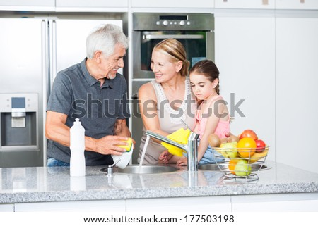 Grandparents and little girl washing dishes, grandfather grandmother and grandchild happy smile on modern kitchen