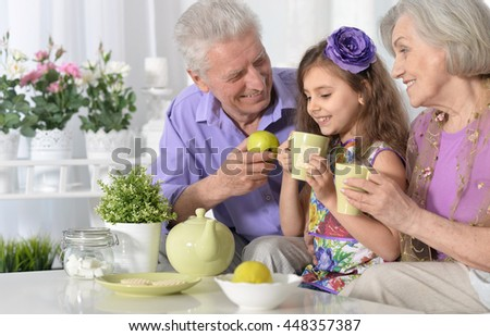 grandparents  and  little girl with tea