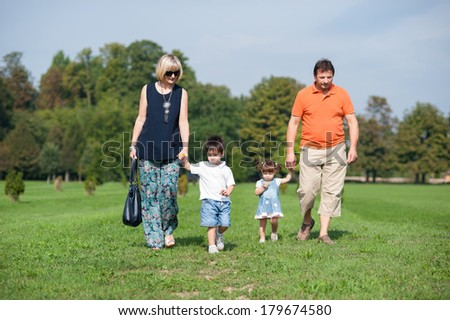 Grandparents and their grandchildren are walking in the park - stock photo