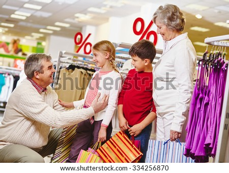 Grandparents and their grandchildren shopping together - stock photo