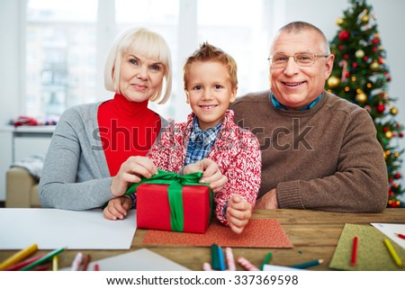 Grandparents and their grandson with giftbox looking at camera on xmas eve - stock photo