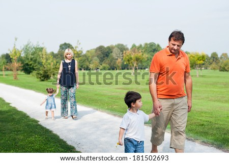 Grandparents are walking on country road with their grandchildren.