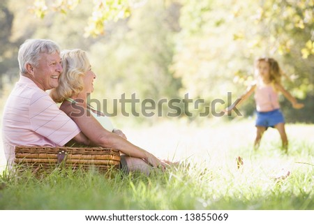 Grandparents at a picnic with young girl in background dancing