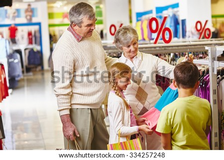 Grandparents choosing new clothes for granddaughter and grandson - stock photo