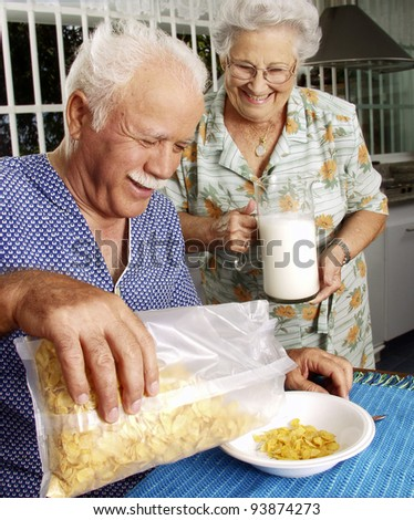 Grandparents eating cereal corn flakes at kitchen. - stock photo