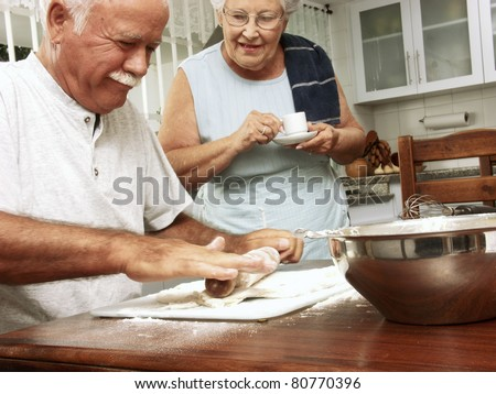 Grandparents enjoying and cooking together in a kitchen. - stock photo