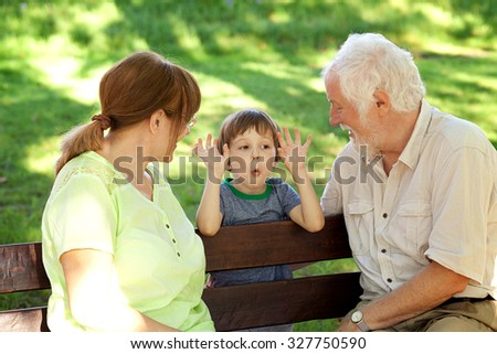 Grandparents having great fun with their grandchild in the park - stock photo