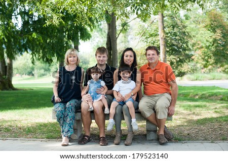 Grandparents, parents and children are sitting on the bench, outside in the park.