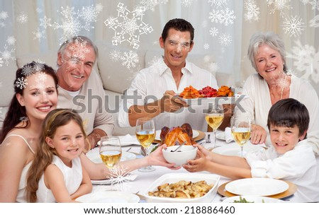 Grandparents parents and children having a family dinner against snowflakes - stock photo