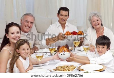 Grandparents, parents and children having a family dinner at home - stock photo