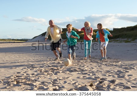 Grandparents Playing Soccer With Grandchildren On Beach - stock photo
