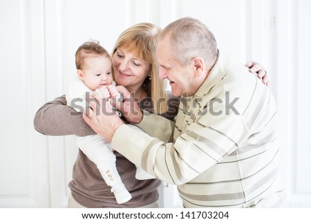 Grandparents playing with a newborn baby girl - stock photo