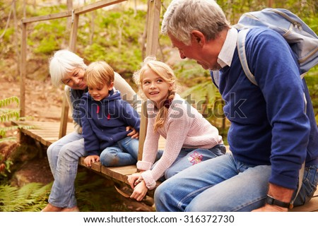 Grandparents sitting with grandkids on wooden bridge - stock photo