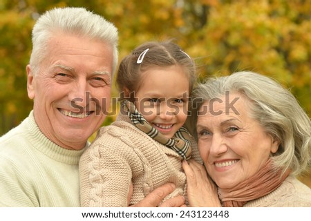Grandparents smiling with granddaughter relaxing in autumn forest